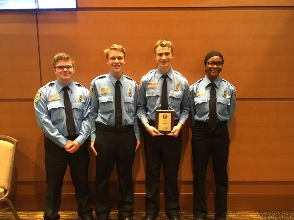 Photo of the four police explorers holding the first place plaque
